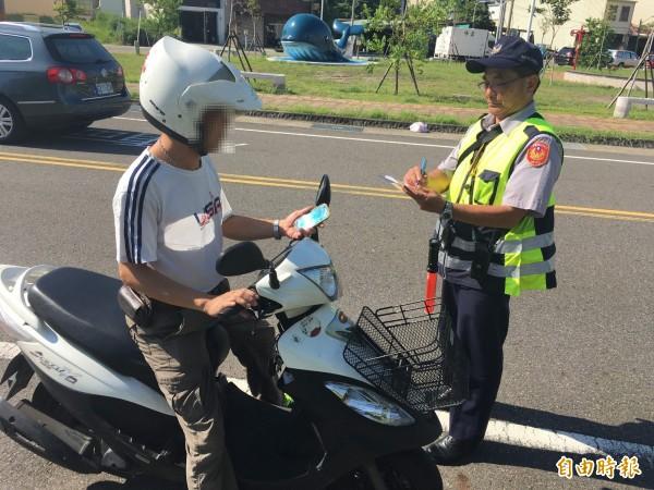 南市警方取締民眾騎機車邊玩手機寶可夢違規狀況。(圖:模擬畫面,記者王俊忠攝)