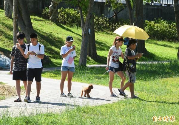 有公司放員工一天「寶可夢假」,並在公園舉辦抓怪大賽。(資料照,記者張嘉明攝)