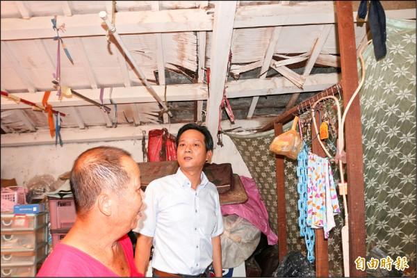 林內鄉長張維崢(右)探視謝家後,立即要求技師在破損的屋頂加蓋帆布,避免再漏水。(記者詹士弘攝)