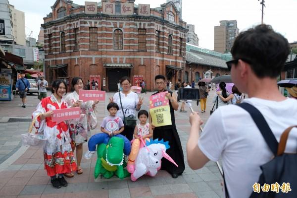 紅絲帶基金會志工,在西門町紅樓廣場推廣戴保險套預防愛滋病觀念,並與民眾進行拍照打卡送套套活動。(記者陳炳宏攝)