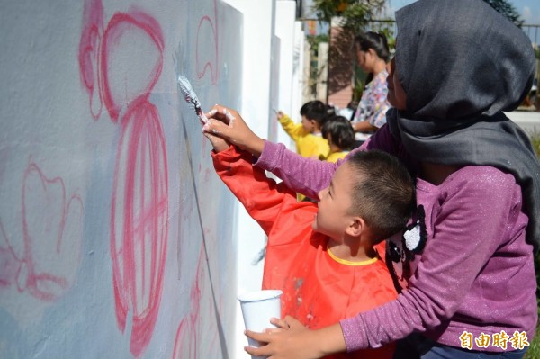 小朋友在國際志工的引導下彩繪兔兔牆。(記者鄭旭凱攝)