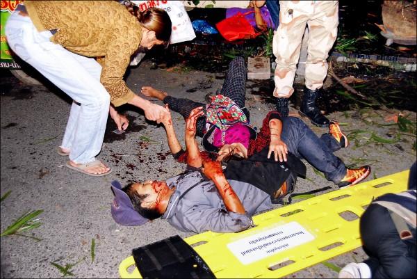 泰國觀光景點華欣十一日、十二日先後傳出四起爆炸案。圖為十一日的兩起爆炸案後,兩名濺血的遊客傷重倒地,一旁的員警及急救人員正設法維持秩序和搶救。 (法新社)