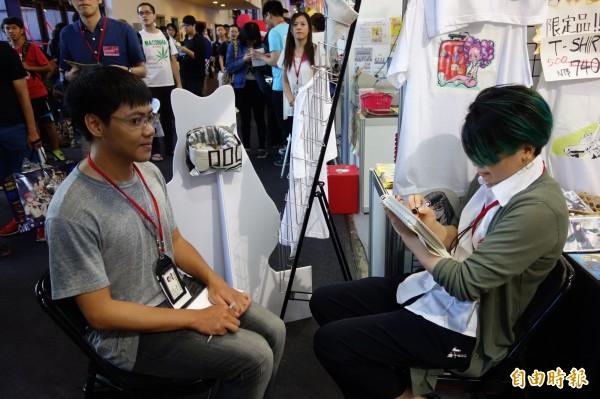日本京都造形藝術大學跨洋來台參加漫畫博覽會,角色設計學系的學生漁野朱香(右),現場直接替記者手繪扇子。(記者吳柏軒攝)