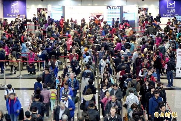 為縮減入境日本的觀光客等待時間,同時吸引更多觀光客赴日,日本政府目前正在研擬實施「入境預先審查制度」。圖為桃園機場出境人潮。(資料照,記者朱沛雄攝)