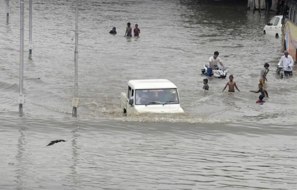 印度近日因遭逢連日暴雨,釀成嚴重災情,許多民眾及動物都被迫遷移,甚至傳出一頭大象被洪水沖離邊境。(法新社)
