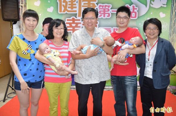 桃園市長鄭文燦和生產三胞胎的林姓夫婦合影,還抱起小嬰兒,儼然是慈父模樣。(記者謝武雄攝)