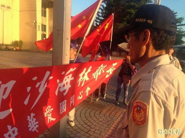 愛國同心會等人在市府前拉起「歡迎沙海林部長」的紅布條;市府駐警見狀後,派兩、三名人員上前制止。(記者何世昌攝)