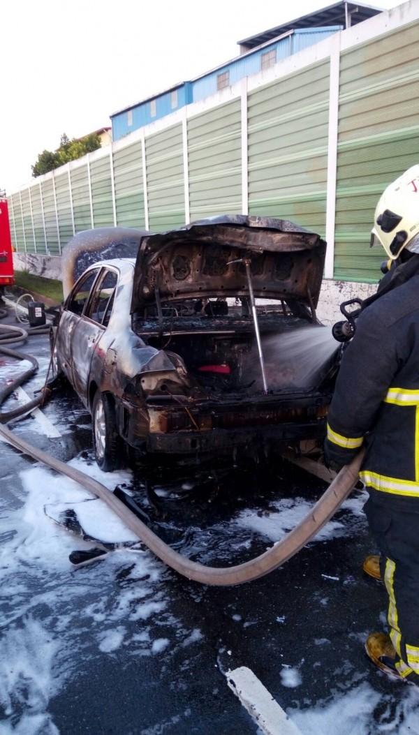 林男汽車竄火,消防隊員趕往灌救。(記者余衡翻攝)