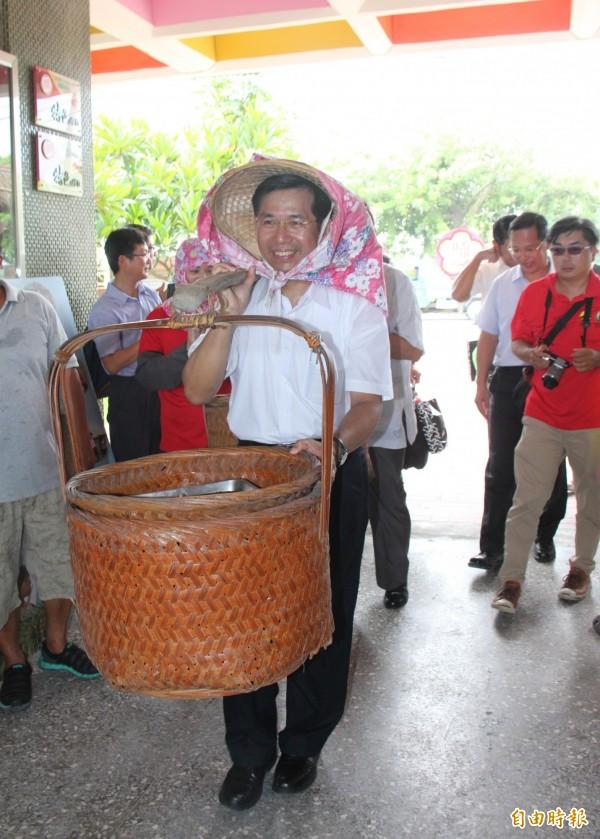 教育部長潘文忠扛著「割稻飯」進場,與大家分享豐收喜悅。(記者陳冠備攝)