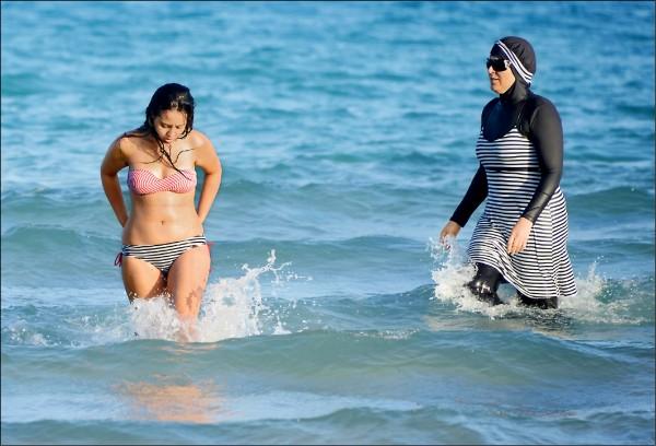 法國多個度假勝地以維護公共安全為由,禁止僅露出臉、手和腳部的穆斯林泳裝「布基尼」,引發正反意見爭辯。但這項禁令也使這款服裝受到更多注意,尤其是非穆斯林女性,買氣紅不讓。圖右為穿著布基尼的突尼西亞婦女。(法新社檔案照)