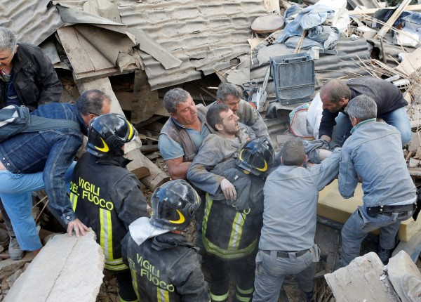 救難人員把被埋在瓦礫堆下的傷者救出。(路透)