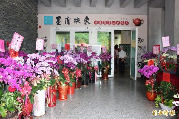書法家林榮森辦個展收到慶賀蘭花和盆景擺滿會場,林榮森全部捐出做義賣。(記者張聰秋攝)