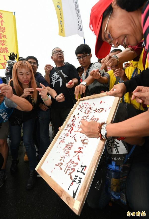勞工團體28日上凱道發起「拒砍七天假!勞團血書上諫 」活動,40位勞工代表用針刺手滴下鮮血,製作「工人血書」,送交總統府血諫。(記者張嘉明攝)