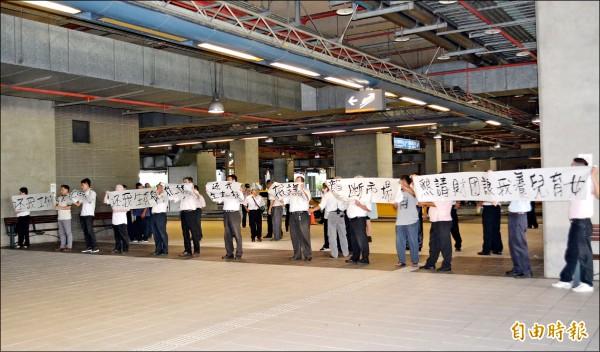 警方取締高鐵台中站違規攬客,卻引起巡迴排班計程車不滿,昨天下午在高鐵站拉白布條抗議。(記者陳建志攝)