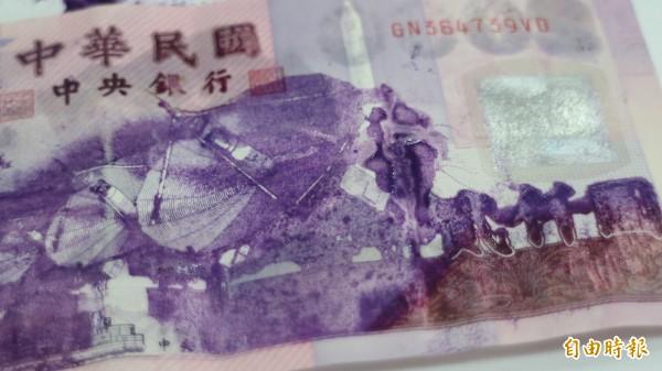 吉安鄉鍾姓男子1年前把2張2000元紙鈔塞入龍柏聚寶盆聚財,今天打開一看紙鈔印刷圖面彷彿被溶解。(記者王錦義攝)