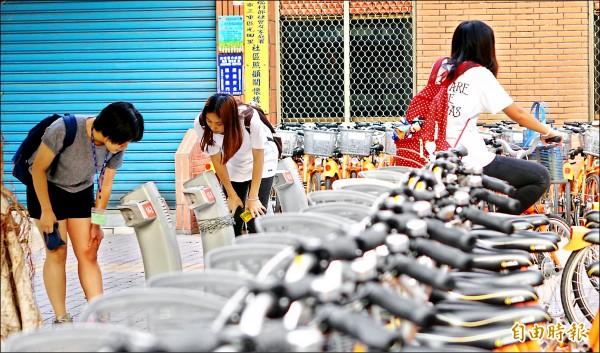 興華公園租借站昨日仍有部分停車柱異常,民眾彎著腰查看異常原因。(記者劉信德攝)