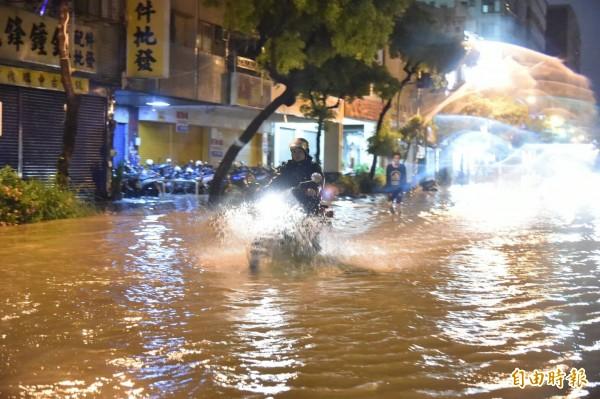 高雄市從今天下午下起間歇性大雨,市區雨量從晚間7點轉大,造成多處路段淹水。(記者張忠義攝)