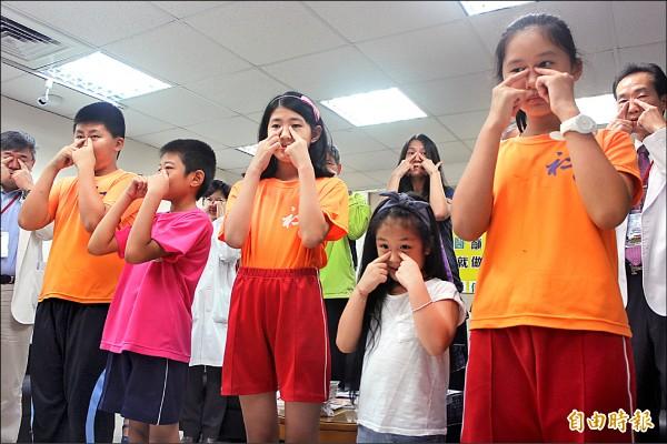 台北市中醫師公會提倡「護眼操」,提醒學童抓寶之餘,也要兼顧眼睛保健。(記者郭逸攝)