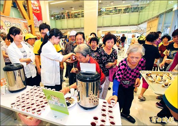 民眾爭相試飲由營養師調配的仙楂飲。(記者張勳騰攝)