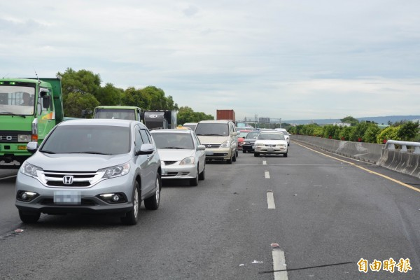 一輛轎車今天上午在中山高彰化路段失控翻覆,造成後方車輛嚴重回堵數公里。(記者湯世名攝)