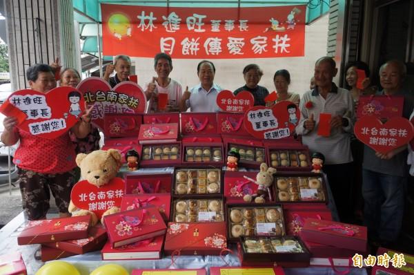 林進旺(中)連續八年贈送愛心月餅,讓家扶受扶助戶好感心。(記者林孟婷攝)