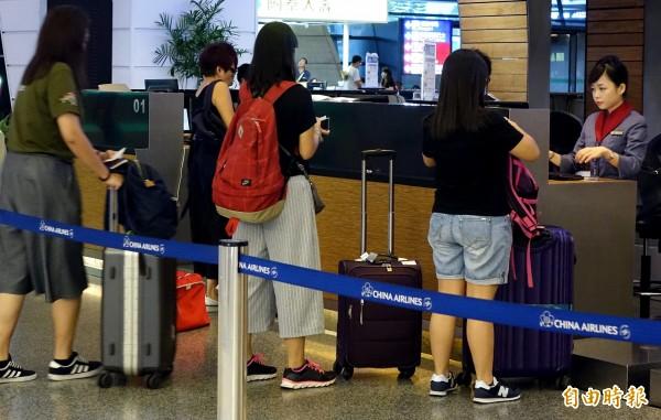 華航9日宣布禁止Note7托運,並建議旅客不要於航程中開機和充電。圖為旅客在桃園機場華航櫃台辦理報到。(記者朱沛雄攝)