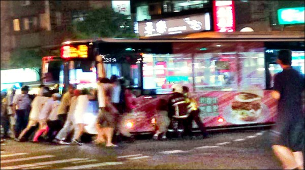 內湖區成功路、金湖路口,一輛公車不慎撞輾過女騎士再拖行10公尺,至少50名路過民眾,合力抬起公車,助女騎士脫困。(記者姜翔翻攝)