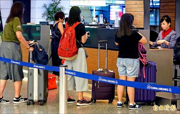 華航昨宣布禁止Note7託運,並建議旅客不要於航程中開機和充電。圖為旅客在桃機華航櫃台辦理報到。 (記者朱沛雄攝)