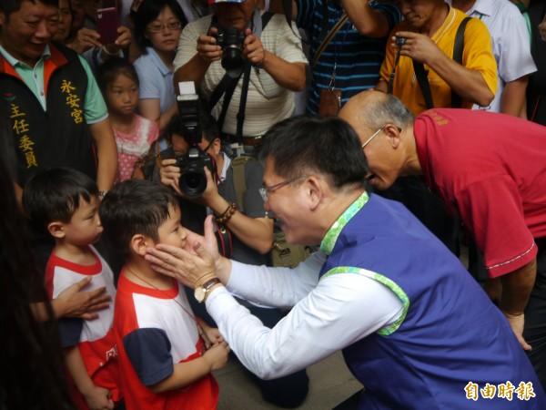林佳龍(右)幫幼童佩戴「神絭」。(記者張軒哲攝)