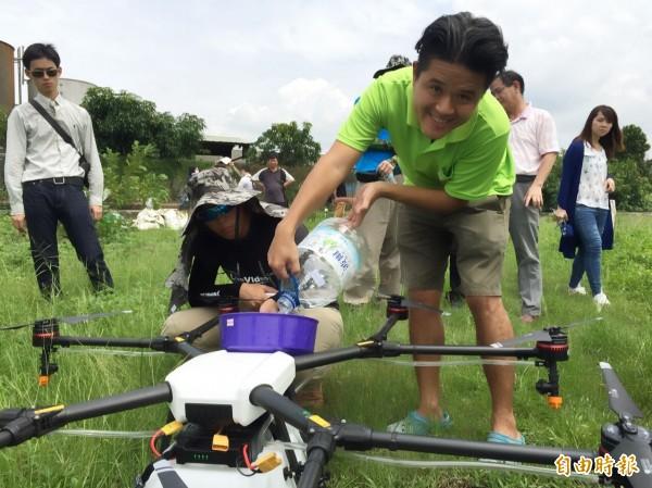 張厚深於無人飛機加入十六公升的農藥,準備高空噴灑農藥。(記者陳文嬋攝)