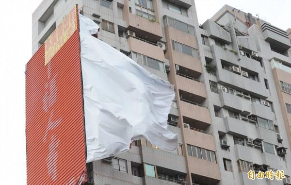 三重區重新路三段,就在三重分局正對面一棟大樓外牆廣告看板遭強風吹毀,一大片帆布廣告在強風中飛揚,發出巨大聲響。(記者劉信德攝)