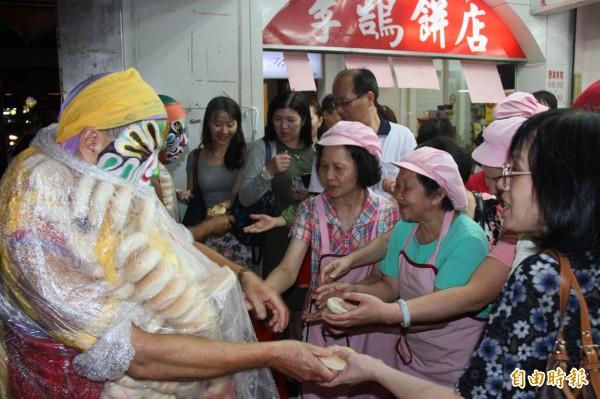 李鵠餅店老員工們都出來向八家將索取鹹光餅。(記者林欣漢攝)