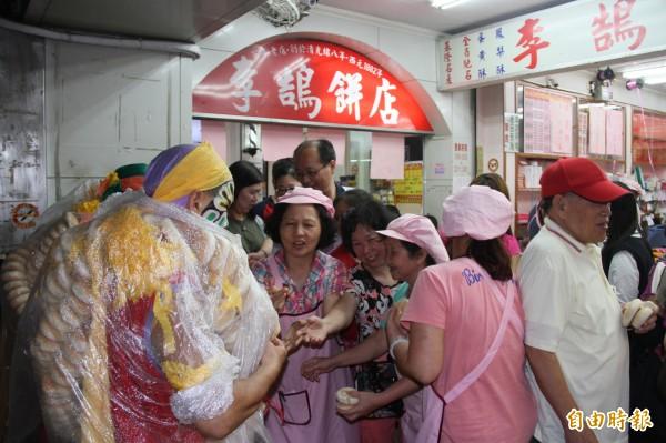 李鵠餅店員工們短暫放下生意,向八家將拿鹹光餅討平安。(記者林欣漢攝)