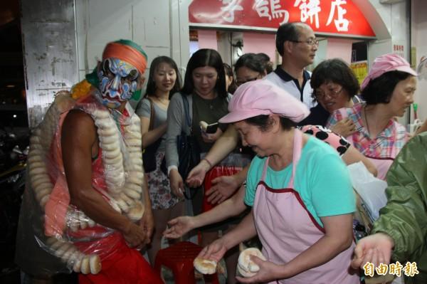 李鵠餅店員工和排隊買月餅民眾都向八家將索討鹹光餅。(記者林欣漢攝)