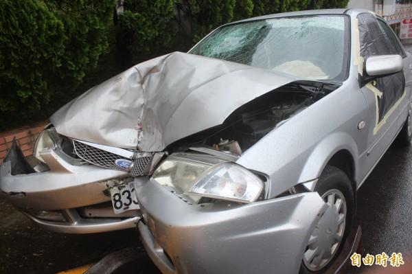 李男座車整個車頭全毀,前座2個車窗因沒關上,昨天深夜處理事故的員警擔心颱風雨淹事故車毀壞相關跡證,特別用膠布封住擋雨。(記者黃美珠攝)