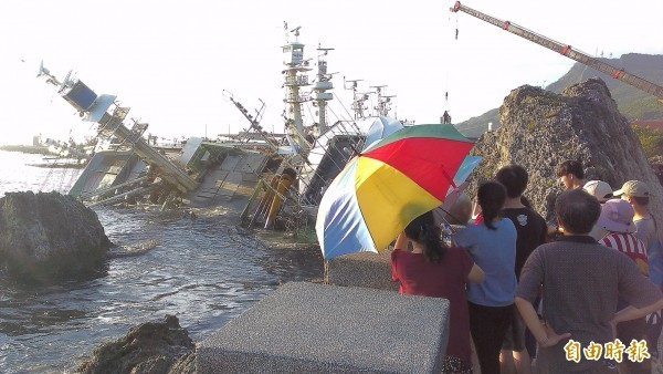圖為民眾擠在西子岸邊觀看翻覆漁船。(記者洪定宏攝)