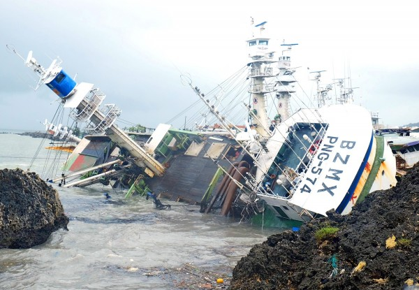 An overturned fishing boat is pictured yesterday at Sizihwan Scenic Area in Kaohsiung after it and three other boats broke loose from their moorings during Typhoon Meranti on Wednesday and floated down the coast.  Photo: Sam Yeh, AFP