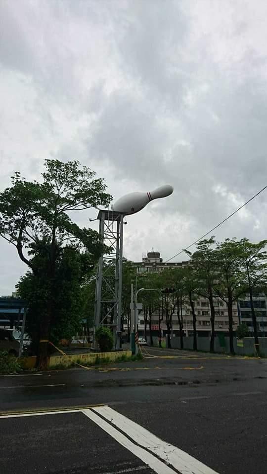 有網友指出,高雄岡山一帶也有保齡球瓶的大型裝飾被強風吹倒後,依舊懸掛於高台上,讓網友笑稱真的是「超越極限」。(圖擷自臉書)