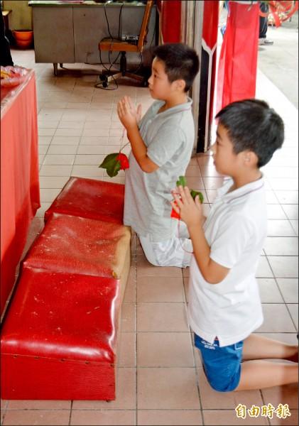 昨天是大里樹王公聖誕,兩位念小學樹王公的「契子」,拿著香火袋虔誠跪地膜拜。(記者陳建志攝)
