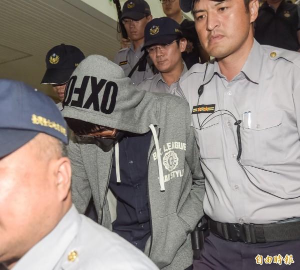 前台大僑生陳皓揚(灰帽T者)22日因殺貓案至台北地院開庭,離去時由大批警力護送,全程低頭不發一語。(記者黃耀徵攝)