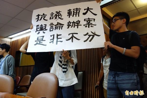 相關系所人士舉布條抗議輔大輿論辦案。(記者葉冠妤攝)