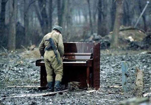 網友找出原圖,表示「俄羅斯士兵(加害者)在車臣土地(受害者)上,彈著自認和平的曲調,多麼雙關又諷刺的畫面。」(擷取自網路)