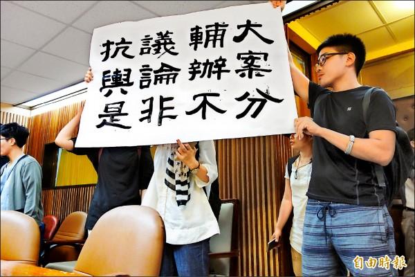 輔大心理系所人士舉布條抗議校方輿論辦案。(記者葉冠妤攝)