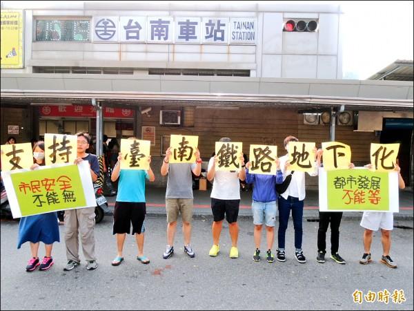 九青年持標語在台南火車站後站表達支持台南鐵路地下化工程的立場。 (記者王俊忠攝)