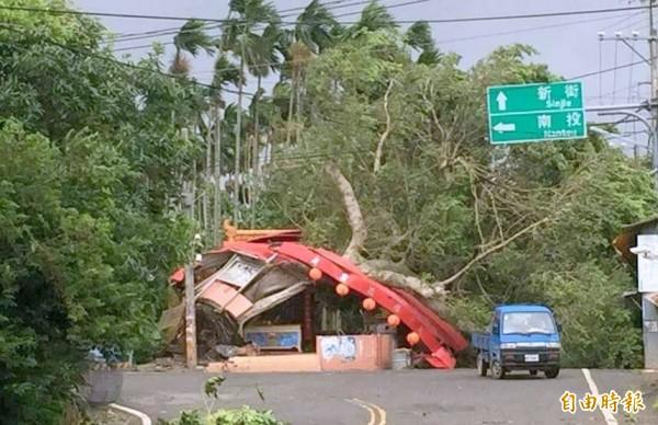 梅姬颱風來襲,南投縣許多路樹倒塌,不但影響交通,甚至壓垮土地公廟與扯斷電纜線,造成停電,警方也忙著維持交通安全。(記者謝介裕攝)