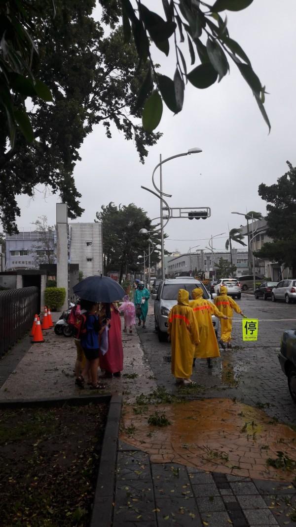 嘉義上午照常上班上課,許多家長中午冒著風雨接送小孩。(記者林宜樟攝)