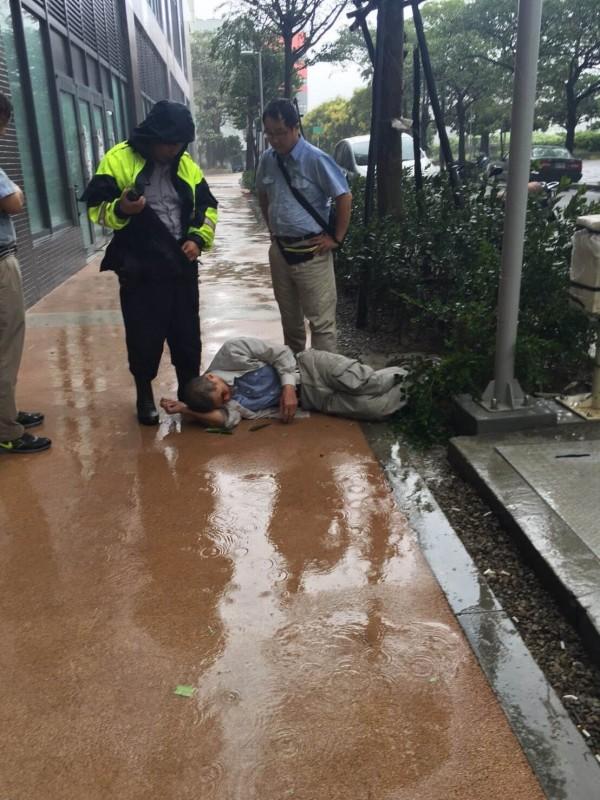 員警脫下雨衣,為謝姓工人遮雨。(記者張瑞楨翻攝)