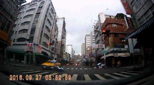 小黃闖紅燈把機車女騎士撞飛,路人見狀無不尖叫驚恐。(記者黃良傑翻攝)