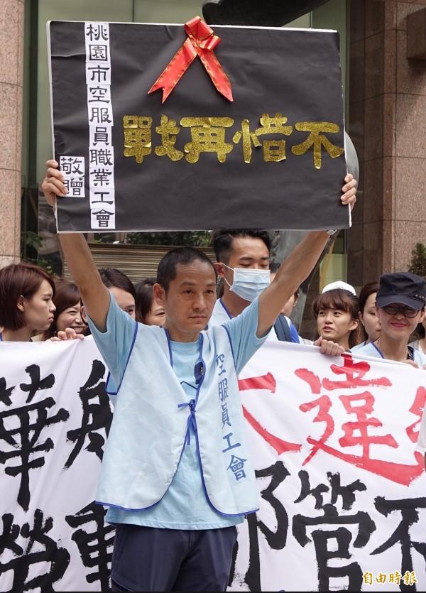 桃園市空服員職業工會理事長趙剛更是高舉看板,強調「不惜再戰」。(記者劉信德攝)