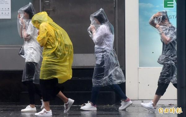 有自稱陽明大學住宿生投訴校方行政人員,讓學生在颱風天冒著風雨外出買食物。示意圖為頂著颱風天風雨外出民眾,非當事人。(資料照,記者簡榮豐攝)